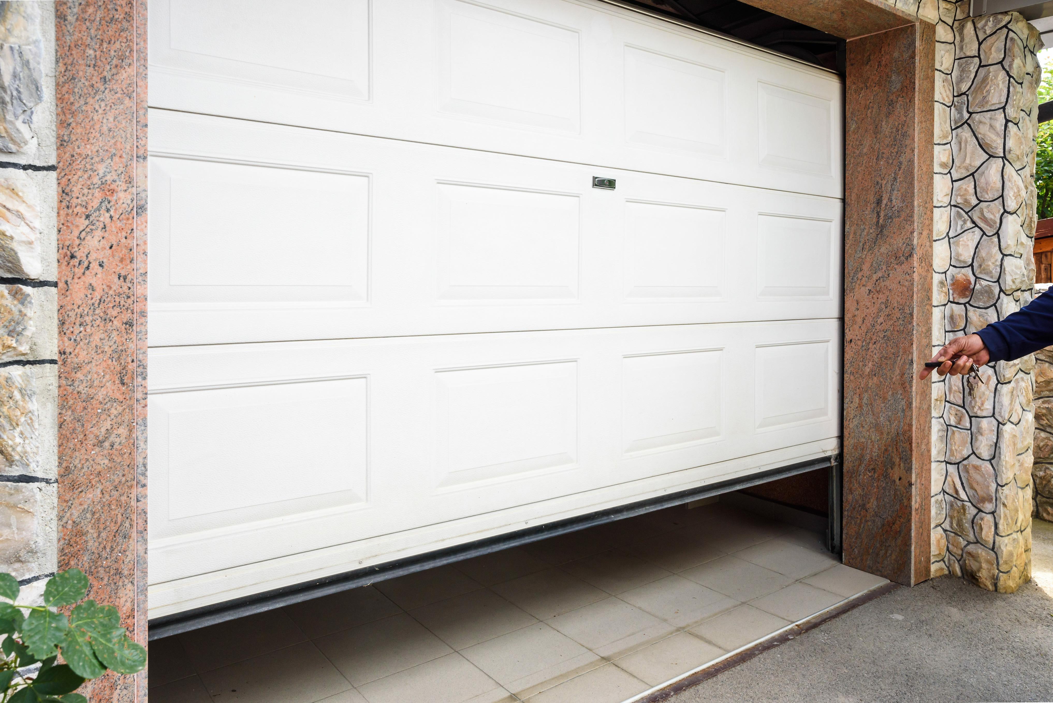 Garage Door Slightly Open As Homeowner Aims An Opener Remote At The Door.
